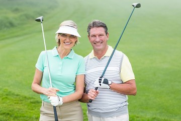 Golfing couple smiling at camera holding clubs