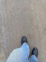 Ноги в джинсах и ботинках идут по замерзшей дороге