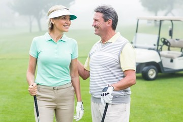 Happy golfing couple facing each other with golf buggy behind