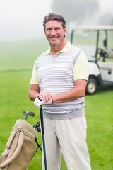Golfer smiling at camera on the putting green