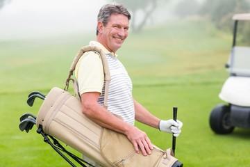 Happy golfer with golf buggy behind