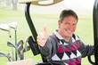 Happy golfer driving his golf buggy smiling at camera - 78785569