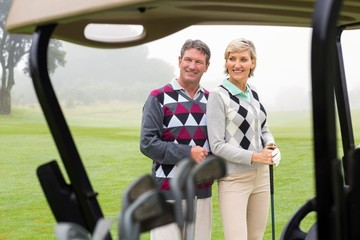 Happy golfing couple smiling