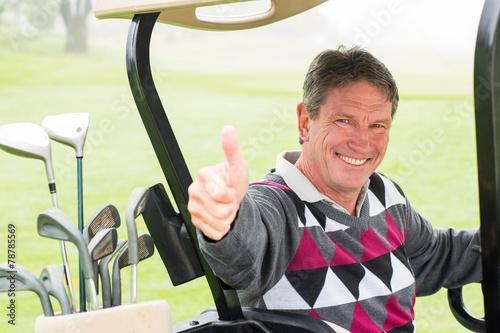 Happy golfer driving his golf buggy smiling at camera