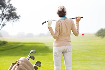 Lady golfer holding her club behind her head