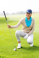 Female golfer kneeing on the putting green