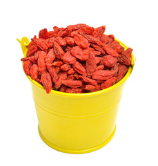 Goji berries in the yellow bucket isolated on white