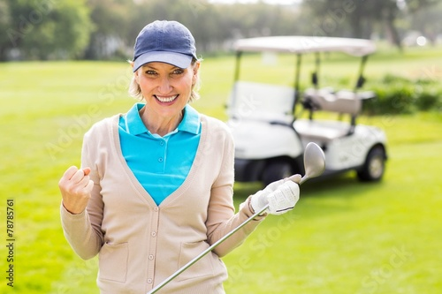canvas print picture Female golfer smiling at camera
