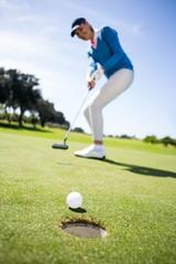 Female golfer putting her ball