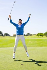 Female golfer leaping and cheering