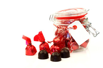 a glass jar full of delicious bonbons wrapped in shiny red paper