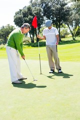 Golfer holding hole flag for friend putting ball