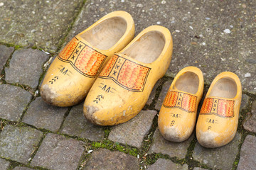pair of traditional Dutch yellow wooden shoes on a stone footpat