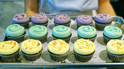 Assorted color cupcakes on tray