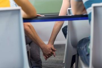 Couple holding hands below desk in classroom