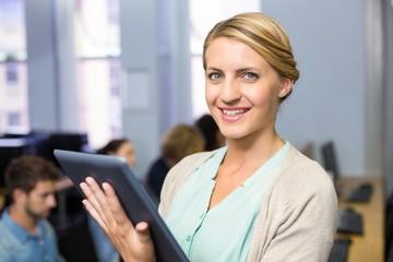Female teacher using digital tablet in computer class