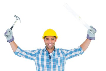 Smiling handyman holding hammer and level