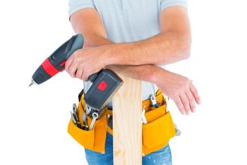 Midsection of male carpenter with power drill and plank
