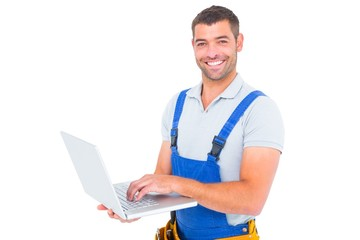 Portrait of smiling handyman using laptop