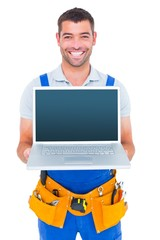 Portrait of smiling repairman showing laptop