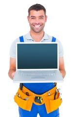 Portrait of smiling repairman showing laptop