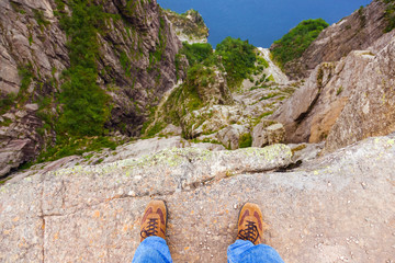 Man standing on cliff Preikestolen in fjord Lysefjord - Norway