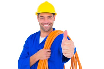 Electrician with rolled wire gesturing thumbs up
