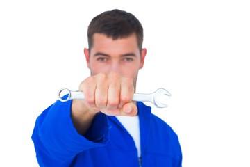 Confident male mechanic holding spanner