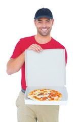 Delivery man showing fresh pizza on white background