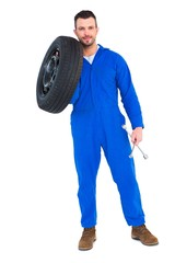 Smiling male mechanic holding tire