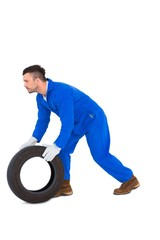 Mechanic holding tire on white background