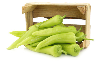fresh green sweet peppers (banana peppers) in a wooden box on a