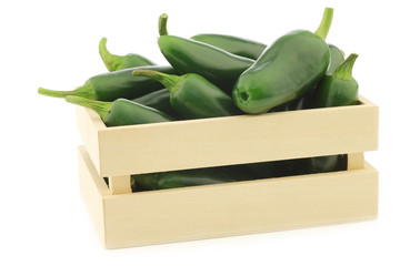 fresh green peppers in a wooden box (capsicum) on a white backgr