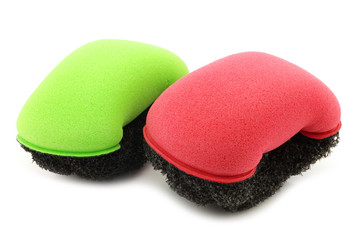 red and green plastic and foam abrasive pads on a white backgrou