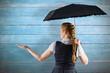 Composite image of pretty redhead businesswoman holding umbrella