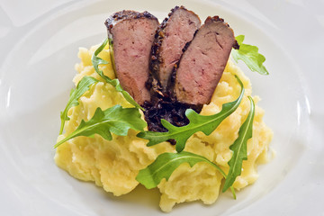 Spice crusted veal liver with mashed potatoes and rocket