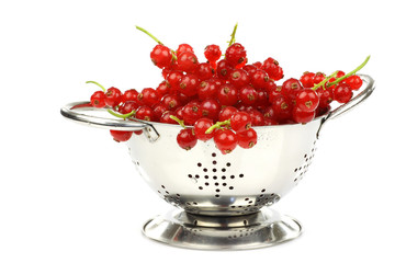 metal colander with a bunch of red currant on a white background
