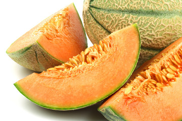 four pieces of cantaloupe melon on a white background