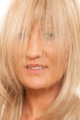 Woman covering her face with long straight hair.