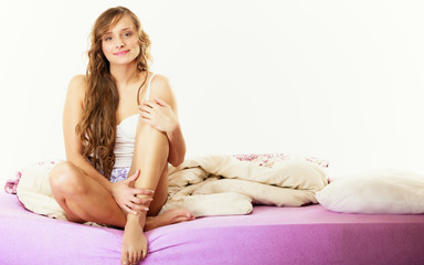 woman long curly hair relaxing on bed at morning
