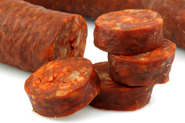 stack of cut chorizo sausage pieces on a white background