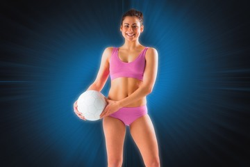 Composite image of fit girl in pink bikini holding ball