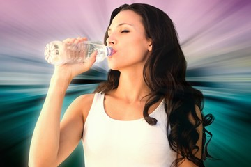 Composite image of brunette drinking water