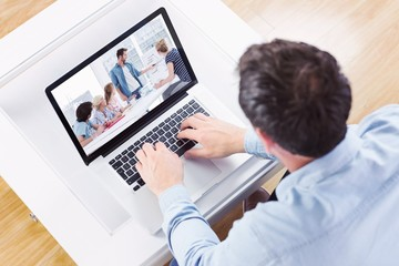 Composite image of high angle view of casual man using laptop