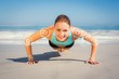 Composite image of fit woman in plank position on the beach