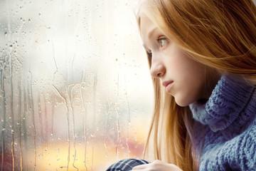 Rainy Day: Girl looking through the Window