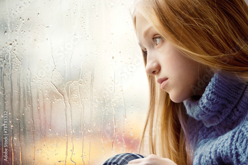 canvas print picture Rainy Day: Girl looking through the Window