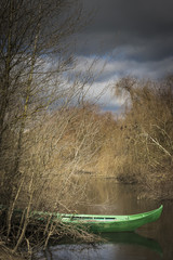 green canoe parked in the shore of a river on a cloudy day