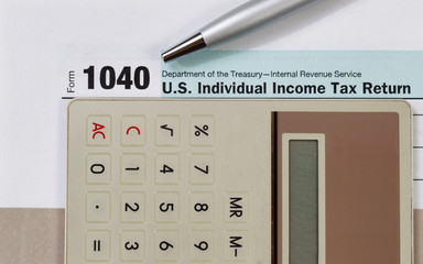 Close up of tax form with pen and calculator