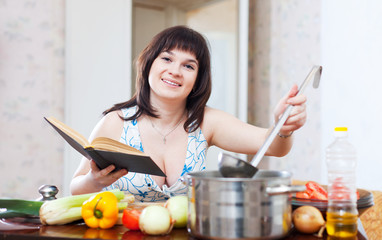 Woman  with book and ladle in kitchen